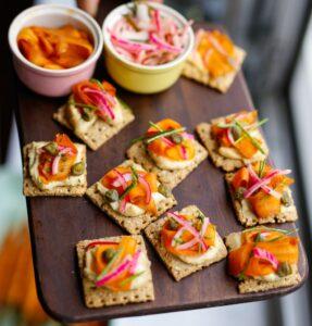 Toastjes Met Cashewcrème En Gemarineerde Wortel In De Hand Vierkant
